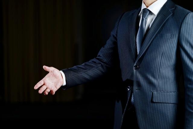 詐欺のイメージ スーツ姿の男性がみ振り手振りで話す様子